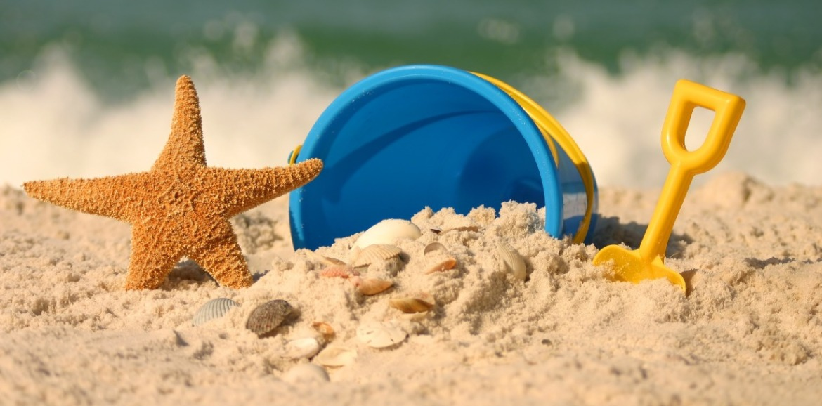 bucket, shovel, and shells on the beach | SeaShore Realty
