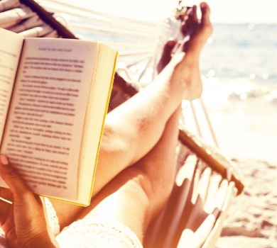 person reading a book on the beach | SeaShore Realty