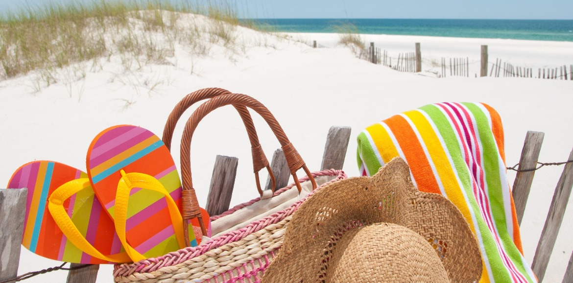 beach items and beach bag sitting on the beach | SeaShore Realty