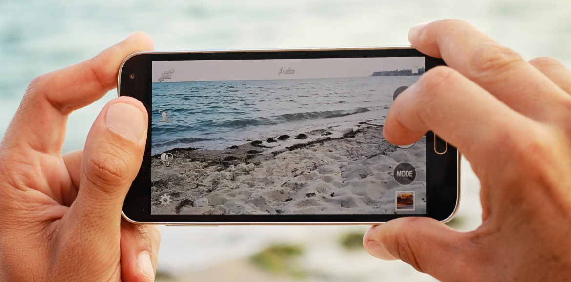 person taking picture of beach with cell phone | SeaShore Realty