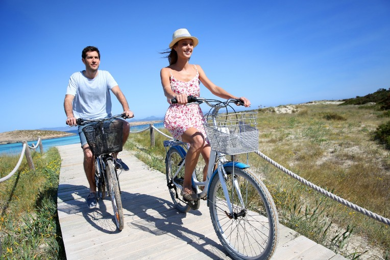 couple riding bicycles at the beach | SeaShore Realty