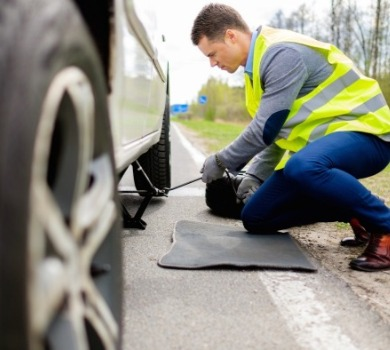 man changing tire alongside the road | SeaShore Realty